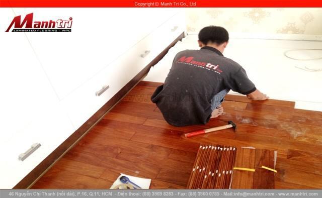 Ván gỗ tự nhiên đang được nhân viên Mạnh Trí lắp đặt