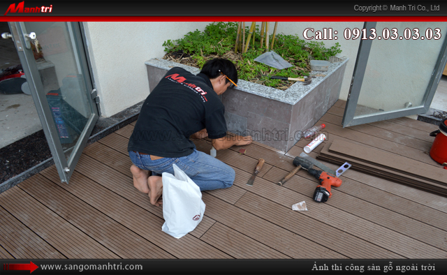 Nhân viên Mạnh Trí đang kiểm tra sàn gỗ ban công ngoài trời