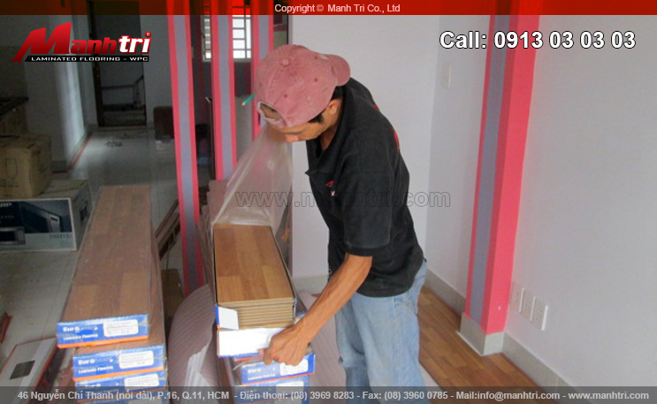 Nhân viên Mạnh Trí lấy thêm gỗ để tiếp tục lắp đặt sàn gỗ