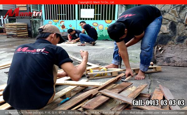 Nhân viên thi công Mạnh Trí đang tháo những cây đinh ra khỏi tấm gỗ Pallet