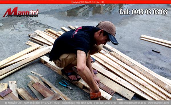 Nhân viên Mạnh Trí tháo đinh từ tấm gỗ thông