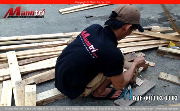 Hình ảnh nhân viên Mạnh Trí tháo donh ra khỏi tấm pallet gỗ