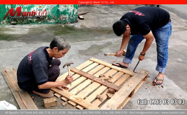 Nhân viên thi công Mạnh Trí tháo tấm gỗ từ pallet