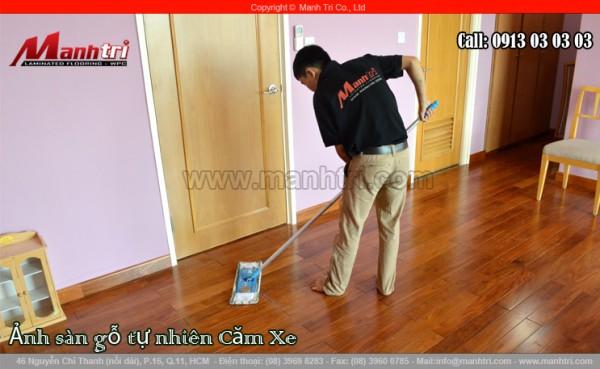 Hình ảnh nhân viên thi công Mạnh Trí dùng cây lau để vệ sinh sàn gỗ