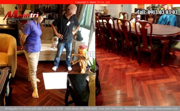 Ảnh nhân viên Mạnh Trí cùng khách hàng đang kiểm tra lại sàn gỗ tự nhiên