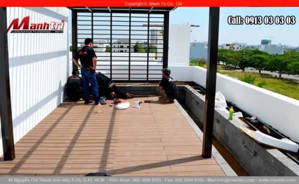 Hình ảnh nhân viên Mạnh Trí đang lắp đặt sàn gỗ nhựa khi nhìn từ xa
