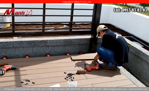 Hình ảnh người thợ thi công đang lắp đặt sàn gỗ ngoài trời tại quận 7, TPHCM