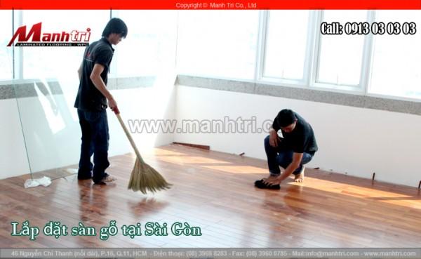 Nhân viên Mạnh Trí vệ sinh sàn gỗ cho sạch bịu bám