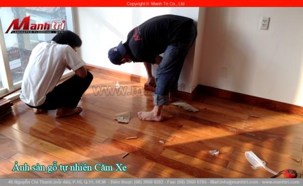 Hình ảnh khách hàng xem nhân viên công ty lắp đặt sàn gỗ tự nhiên Căm Xe