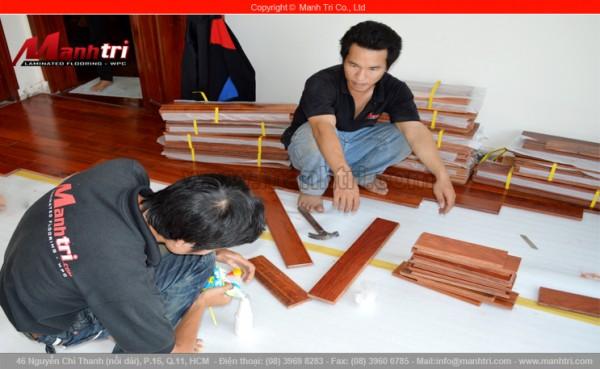 Ảnh cận cảnh nhân viên Mạnh Trí lắp đặt len chân tường sàn gỗ