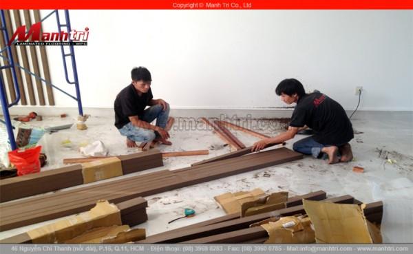Hình ảnh những người thợ thi công Mạnh Trí đang cắt thanh lam gỗ nhựa