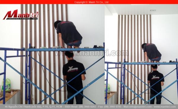 Hình ảnh nhân viên Mạnh Trí đang lắp đặt thanh lam gỗ nhựa ốp tường
