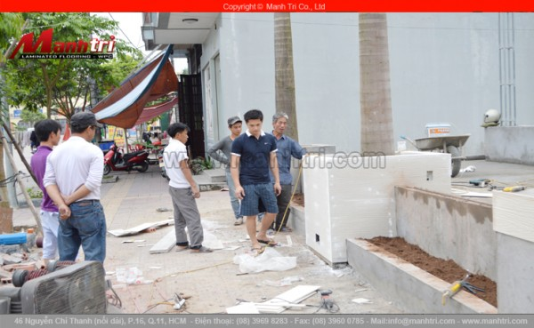 Hình ảnh nhân viên Mạnh Trí đang ốp những tấm xi măng giả gỗ