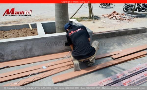 Hình ảnh nhân viên Mạnh Trí cắt thanh gỗ Conwood để ốp chậu trang trí