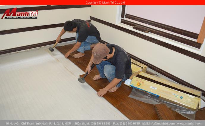 Hình ảnh nhân viên Mạnh Trí lắp đặt sàn gỗ công nghiệp công nghệ Đức