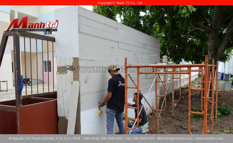 Hình ảnh nhân viên Mạnh Trí đang ốp tường gỗ Conwood ngoài trời